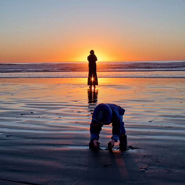 Child with Mother at Beach During Sunset